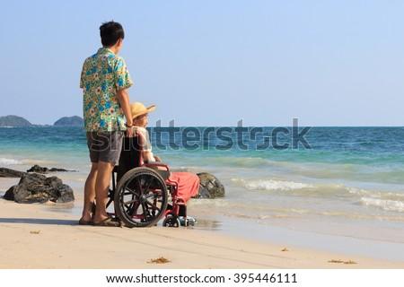 Welcome summer beach grandma wheelchair took. - stock photo