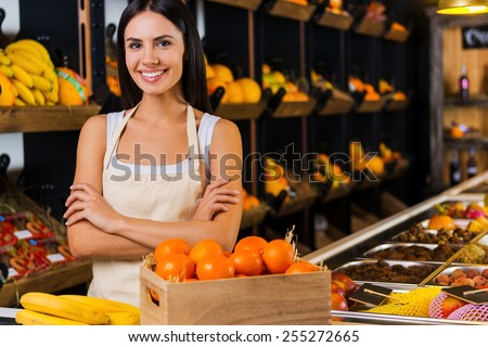 Welcome to fruit paradise! Beautiful young woman in apron keeping arms crossed and smiling while standing in grocery store with variety of fruits in the background  - stock photo