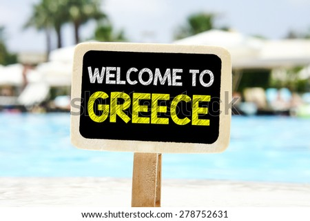 Welcome to Greece on chalkboard. Welcome to Greece text written on chalkboard near pool - stock photo
