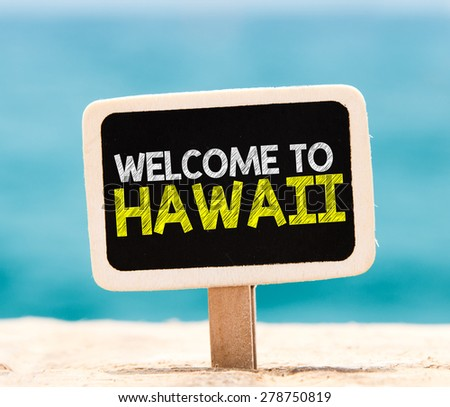 Welcome to Hawaii on chalkboard. Welcome to Hawaii text written on chalkboard, on beach - stock photo