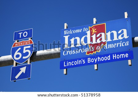 Welcome to Indiana and highway65 road sign against blue sky. - stock photo