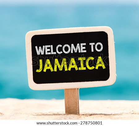 Welcome to Jamaica on chalkboard. Welcome to Jamaica text written on chalkboard, on beach - stock photo
