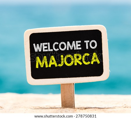 Welcome to Majorca on chalkboard. Welcome to Majorca text written on chalkboard, on beach - stock photo
