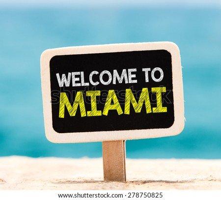Welcome to Miami on chalkboard. Welcome to Miami text written on chalkboard, on beach - stock photo