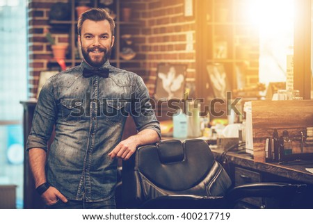 Welcome to my barbershop! Cheerful young bearded man looking at camera and holding hand in pocket while leaning on chair at barbershop - stock photo