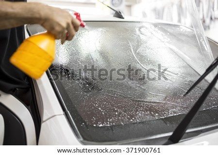 Welcome to our car service station. Closeup image of a car mechanic man attaching tinting film foil to car window in specialized service station