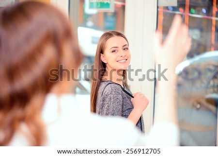 Welcome to our salon again. Rear view of hairdresser saying good bye and waving her hand to her satisfied client in the beauty salon - stock photo