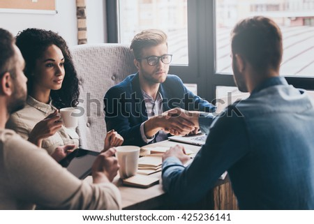 Welcome to our team! Two men shaking hands and looking at each other while their coworkers sitting at the business meeting  - stock photo