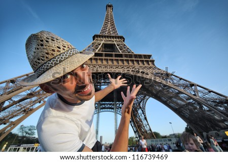 Welcome to Paris! Happy smiling tourist pointing to Eiffel Tower in Paris, France. - stock photo