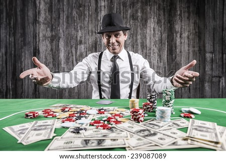 Welcome to play! Smiling senior man in shirt and suspenders sitting at the poker table and gesturing with money and gambling chips laying near him - stock photo