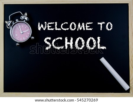 Welcome to School concept with clock on table in front of chalkboard