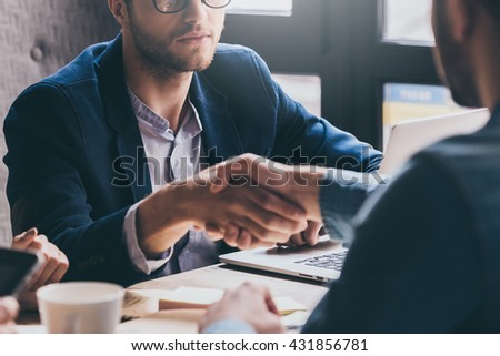 Welcome to team! Close-up of two businessmen shaking hands while sitting at the desk - stock photo