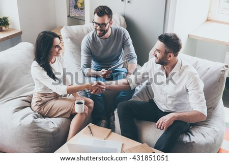 Welcome to team! Top view of three young cheerful business people sitting together at the desk while man and woman shaking hands  - stock photo