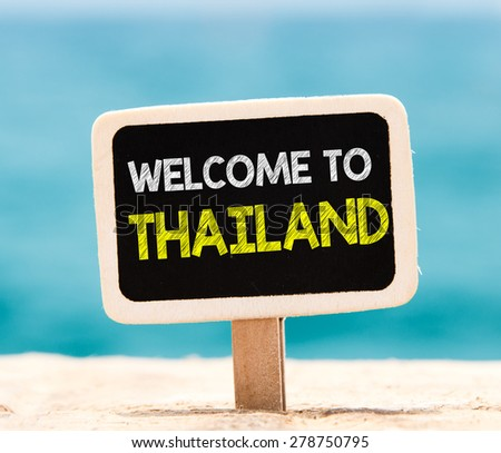 Welcome to Thailand on chalkboard. Welcome to Thailand text written on chalkboard, on beach - stock photo