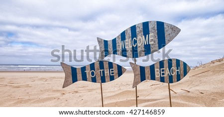 Welcome To The Beach whimsical signs in the shape of striped fish stuck in The sand with the ocean in the background. Concept  for vacation, seaside, summer, fun, relaxation, escape - stock photo