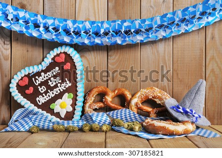 welcome to the Oktoberfest  - original bavarian gingerbread heart with Oktoberfesthat and soft pretzels from Germany in front of olt wooden board - stock photo