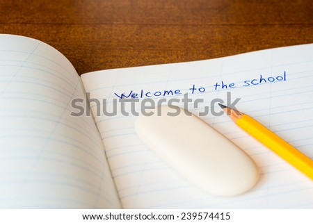 Welcome to the school, an exercise book and pencil with eraser on the wooden table