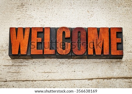 welcome word in vintage letterpress wood type stained by red ink on a grunge white  painted barn wood - stock photo