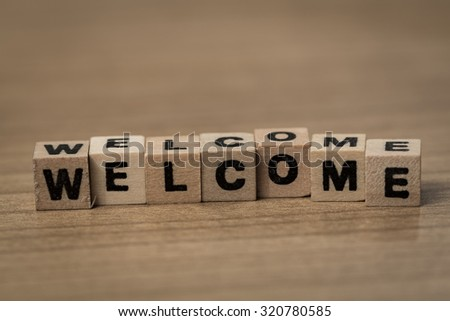 Welcome written in wooden cubes on a desk - stock photo