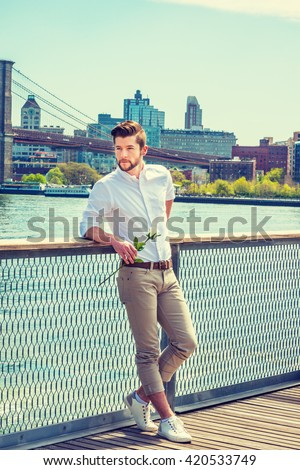Welcome You. I missing you. American man with beard, wearing white shirt, tan pants, white sneakers, holding white rose, standing by fence at harbor in New York. Brooklyn, bridge, boat on background. - stock photo