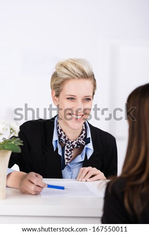 Welcoming beautiful elegant young hotel receptionist smiling at a guest as she greets her at the reception desk for checking in - stock photo