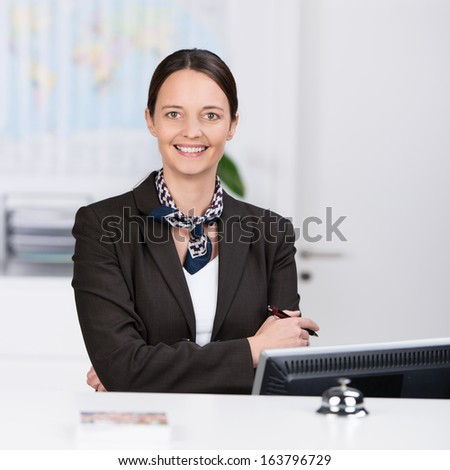 Welcoming confident friendly receptionist standing behind a hotel reception desk with her arms folded giving the camera a beautiful warm smile - stock photo