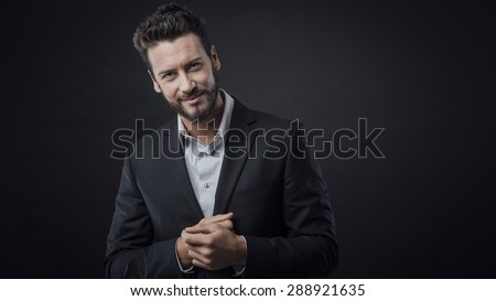 Welcoming friendly businessman smiling at camera on dark background - stock photo