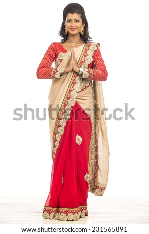 Welcoming Indian young girl in traditional saree on white. - stock photo