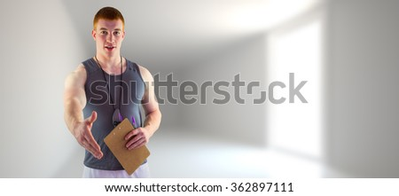 Welcoming personal trainer giving handshake against bright hall with windows - stock photo