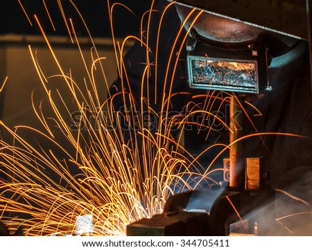 Welder and bright sparks. Construction and manufacturing, motion blur - stock photo