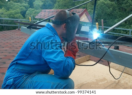 Welder at the factory working with metal construction - stock photo