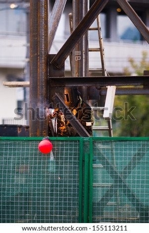 Welder at work at the construction site surrounded by green fence - stock photo