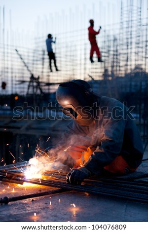 Welder does the job.Workers erecting steel in the background - stock photo