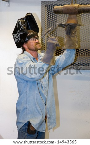 Welder hammering a piece of metal he's been welding.  Focus on the man's face.  (helmet was customized by the welder - the designs are not trademarked or copyrighted) - stock photo