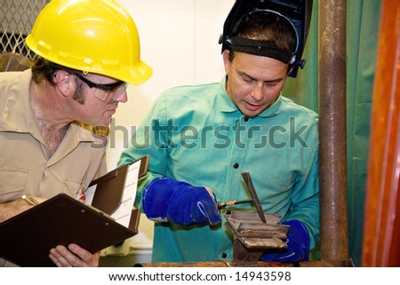 Welder hammering metal as an auditor looks on inspecting his work.  Focus on the welder.   All work is accurately depicted in accordance with industry  code and safety standards. - stock photo