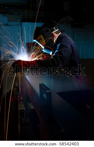 Welder in fabrications factory constructing a metal box section. - stock photo
