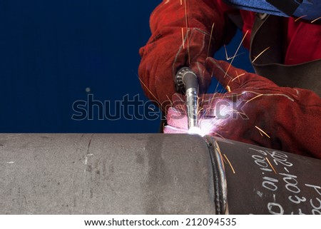 welder in factory with protective equipment welding pipe - stock photo
