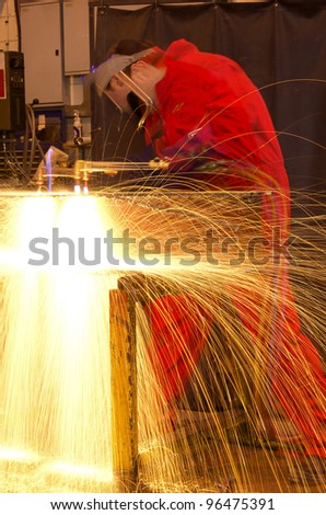 Welder in workshop manufacturing metal construction with multi-exposure blur on man - stock photo