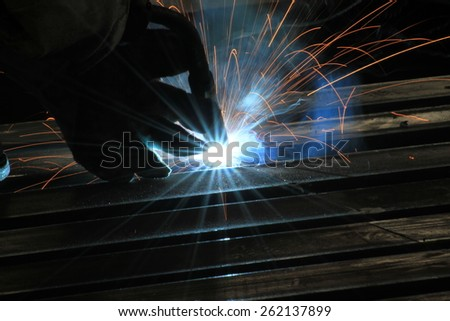 welder is welding steel pipe with spark and light - stock photo