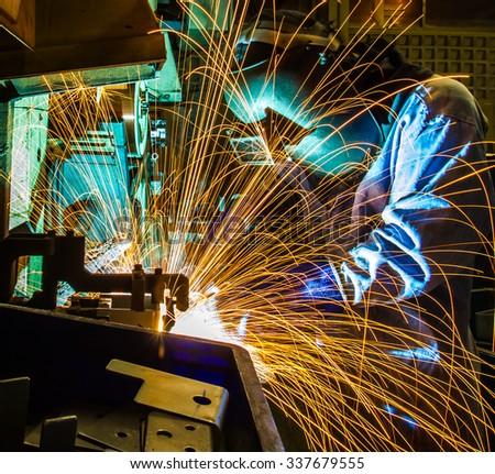 Welder movement Industrial automotive part in factory - stock photo