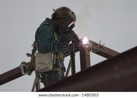 Welder on steel structure, high-rise construction project - stock photo