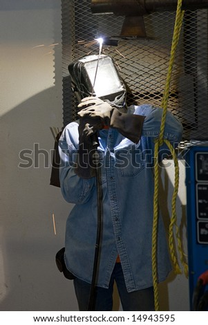 Welder properly outfitted in safety gear, welding metal over his head.  (the pattern on the helmet was done personally by the welder and is not a logo or trademark) - stock photo