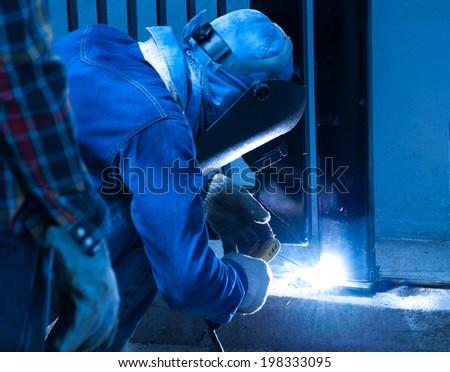 Welder repairing the metal fence - stock photo
