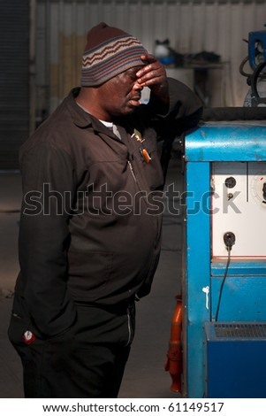 Welder standing with hand on forehead and sleeping - stock photo