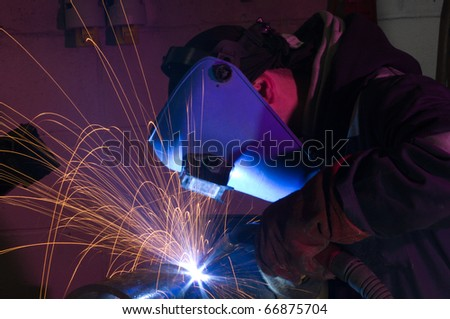 Welder uses MIG torch to make sparks during manufacture of metal equipment.