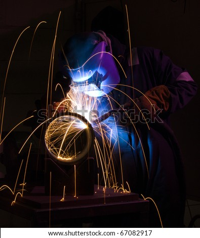 Welder uses torch to make sparks during manufacture of metal cylinder. - stock photo