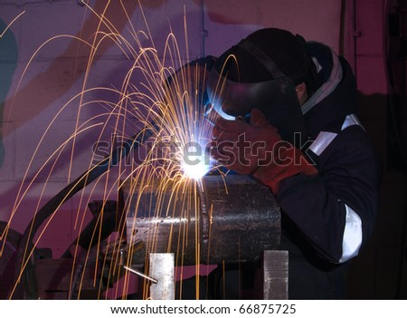 Welder uses torch to make sparks during manufacture of metal equipment. - stock photo