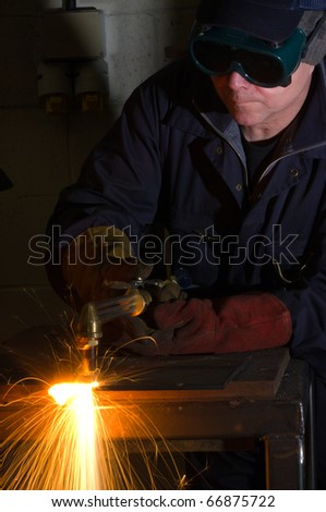 Welder uses torch to make sparks during removal of weld from metal equipment. - stock photo