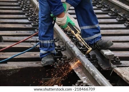 Welder using cutting torch to cut a rail - stock photo