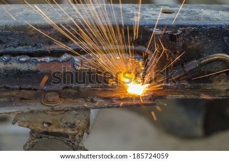 welder using torch on metal object - stock photo